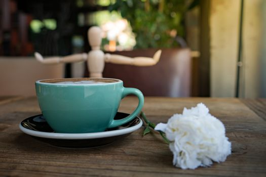 Hot mocha coffee or capuchino with white carnation flower and wo