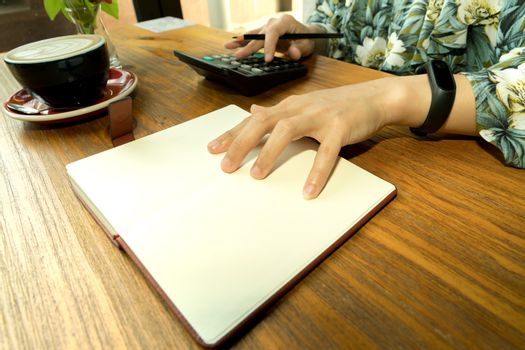 business women is calculating the expense on the wooden table wi
