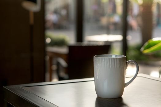 A mocha or cappuccino hot coffee in white cup on the wooden tabl