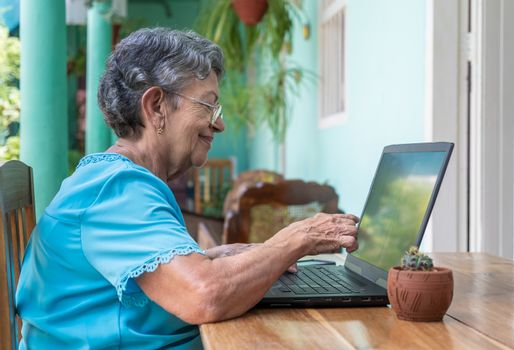 Smiling elderly woman wearing glasses with a laptop