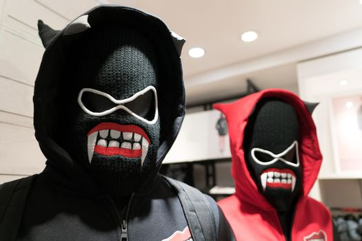 a demons mask, a couple anorak in black and red costume on devil