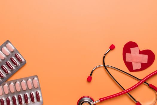 healthcare and medical concept red stethoscope and medicine on t
