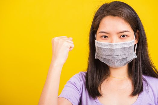Asian beautiful happy teen young woman wearing face mask protective, COVID virus and air pollution her raise hands glad excited cheerful after recovering from illness isolated on yellow background
