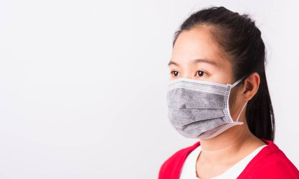Asian adult woman wearing red shirt and face mask protective against coronavirus or COVID-19 virus or filter dust pm2.5 and air pollution she looking side, studio shot isolated white background