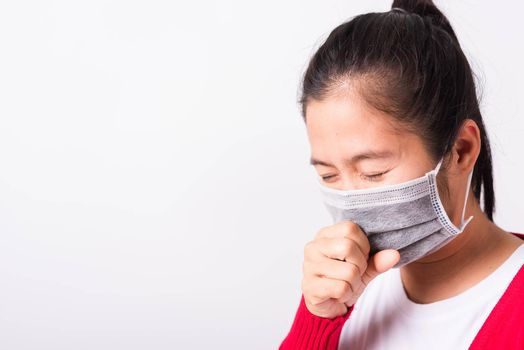 Asian adult woman wearing red shirt and face mask protective against coronavirus or COVID-19 virus or filter dust pm2.5 and air pollution her sneezing use hand close mouth, isolated white background