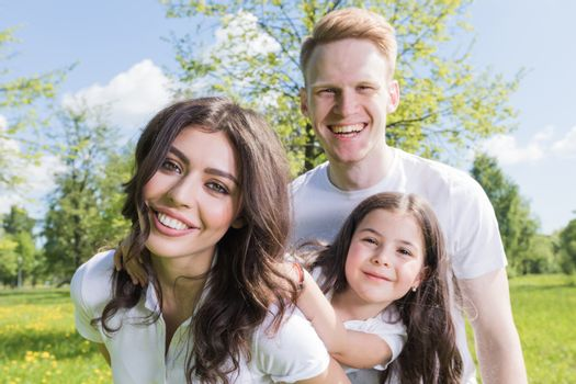 Happy family having fun outdoors in spring park against natural green meadow and trees background