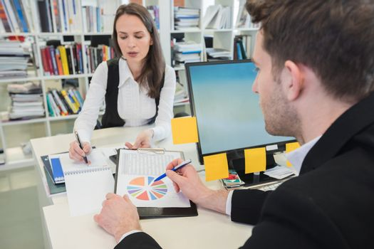 Young business people studying statistics data in office