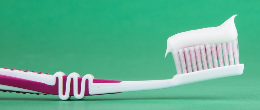 toothbrush with toothpaste isolated on a green background