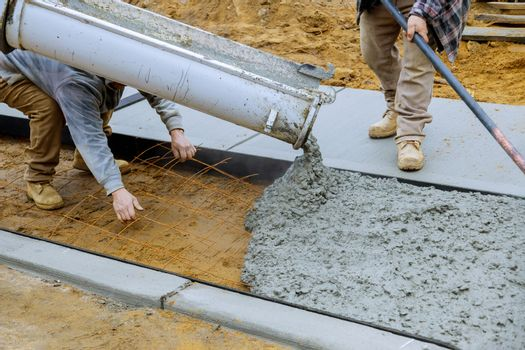 Pouring concrete to create in the walking sidewalk under construction