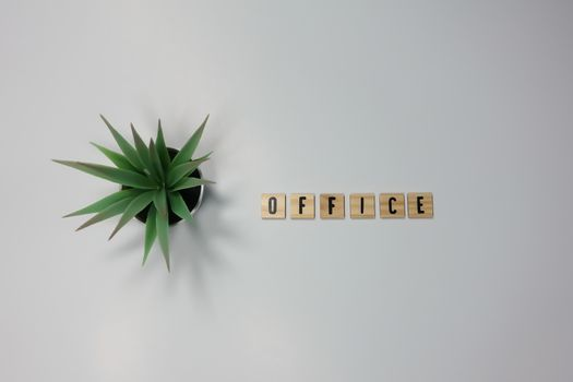 The word Office written in wooden letter tiles on a white background.
