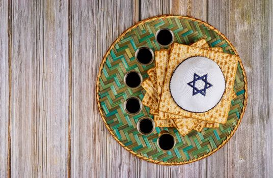 Passover matzoh jewish holiday bread and six glasses kosher wine over wooden table background.