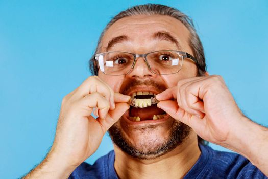 Man's hand putting dental implant temporary