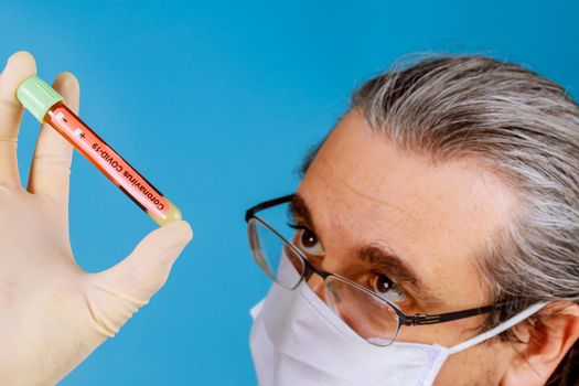 Doctor in face mask a blood test tube sample to check COVID-19 coronavirus