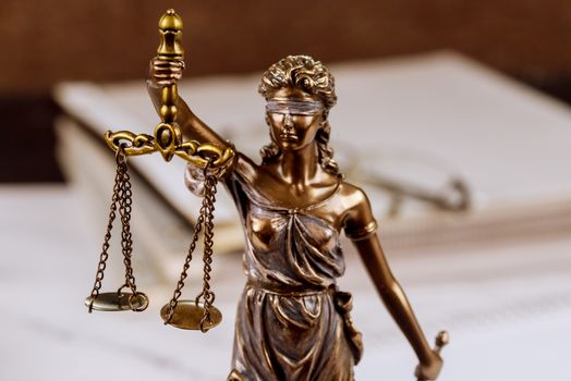 Statue justice scales law lawyer pile of unfinished documents on law office desk
