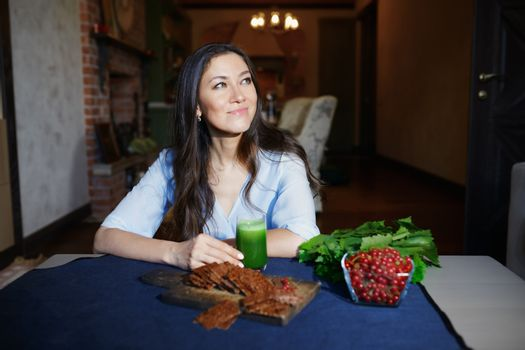 Smiling vegetarian woman sitting at the table with celery fresh juice, flaxseed bread and berries
