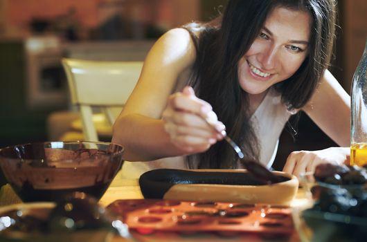 Staying at home woman preparing handmade vegetarian chocolate truffles