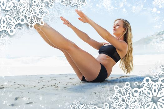 Fit blonde in core balance pilates pose on the beach against snow