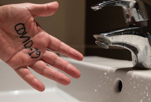 Conceptual close up shot of the left hand of a Caucasian man. The word covid-19 appears on the palm, just next to the sink tap.