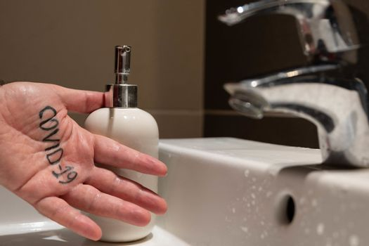 Conceptual close up shot of the left hand of a Caucasian man. On the palm there is the word covid-19, immediately next to the sink tap and the soap dispenser. Hygienize, wash away the virus.
