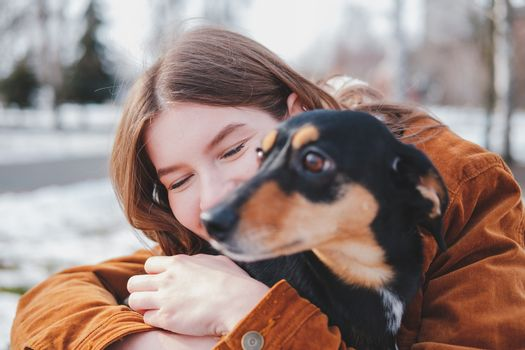Human being happy with a dog. Loving pets concept: happy young woman hugs her dachshund at a walk, selective focus