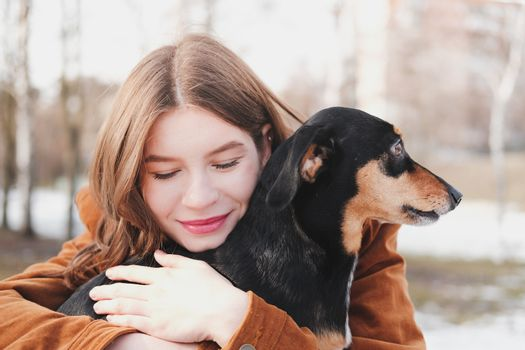 Human being happy with a dog. Loving pets concept: happy young woman hugs her dachshund at a walk