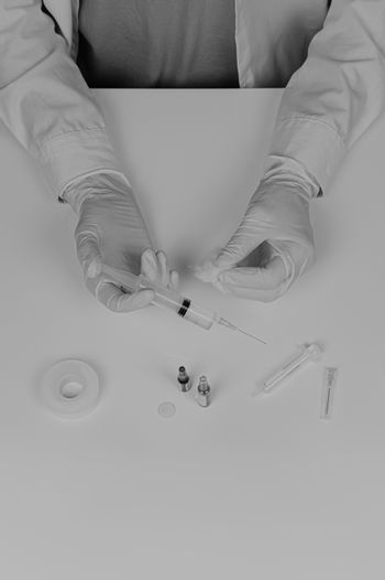 MD preparing injection, faded monochrome style. Top view of medical doctor hands in gloves and lab coat holding syringe on white table with medical accessories