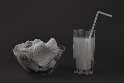 Bowl of potato chips and glass of orange drink in dark monochrome background. Minimalistic image of attention grabbing snacks and beverage