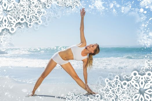 Gorgeous blonde standing in extended triangle pose by the sea against snow