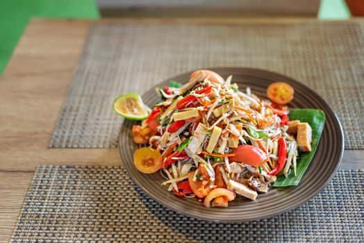 Traditional thai cuisine spicy green papaya salad with rice vermicelli