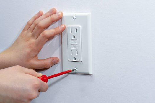 Attaching a white platband to an electrical wall outlet