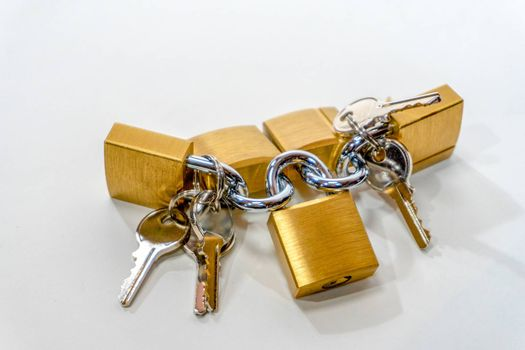 Small bronze locks with steel keys lie on a white background