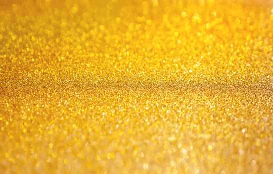 Golden abstract background with shiny glitter. Festive sparkling macro texture. Holiday backdrop with copy space.