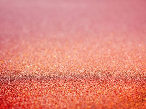 Red abstract background with shiny glitter. Pink festive sparkling macro texture. Holiday backdrop with copy space.