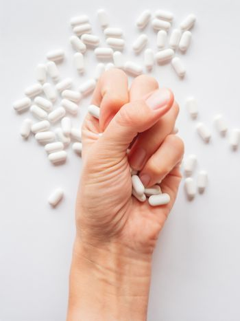 Palm hand full of white scattering pills. Woman gripes hand with capsules with medicines on light background. Flat lay, top view.