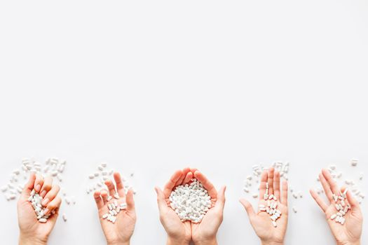 Palm hands full of white scattering pills. Woman gripes hand with capsules with medicines on light background. Flat lay, top view.