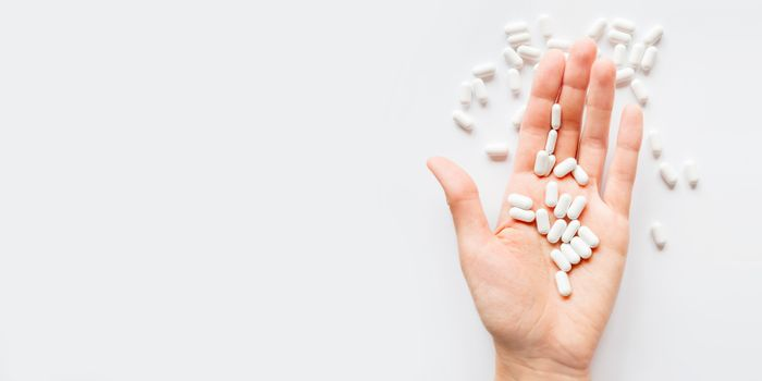 Palm hand full of white scattering pills. Capsules with medicines on light background. Flat lay, top view.