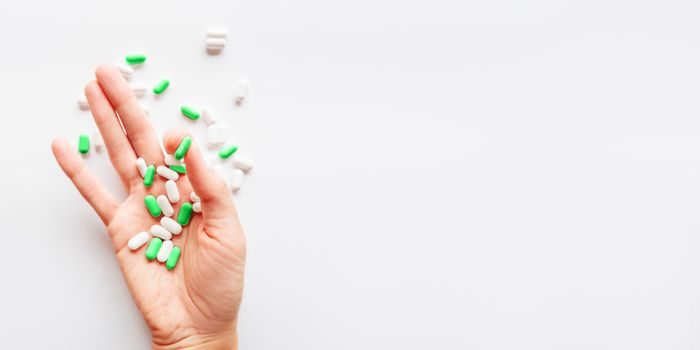 Palm hand full of white and green scattering pills. Capsules with medicines on light background. Flat lay, top view.