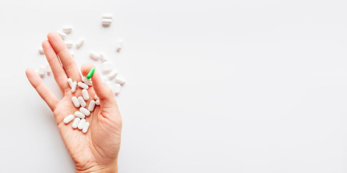 Palm hand full of white and green one scattering pills. Capsules with medicines on light background. Flat lay, top view.