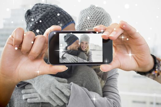Hand holding smartphone showing against snow