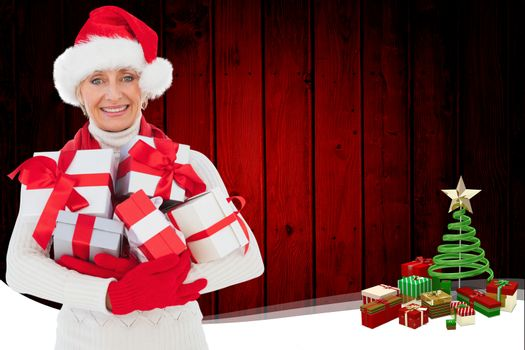 Festive woman holding gifts against christmas themed frame with tree