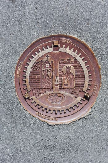 Metal sewerage hatchway with bas relief. Iron manhole with histo