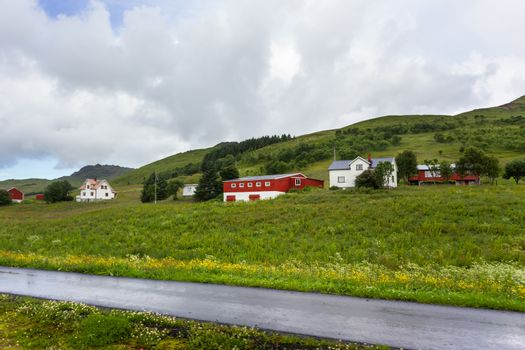 Beautiful scandinavian landscape with meadows, mountains and vil