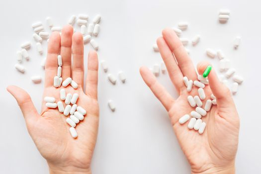 Palm hands full of white and green one scattering pills. Capsule
