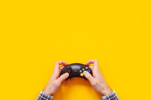 Man's hands with wireless gamepad on yellow