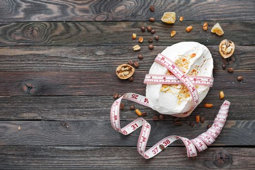 Rustic wooden background with meringue and tailor's ruler. Diet concept. Unhealthy eating. Top view, place for text.