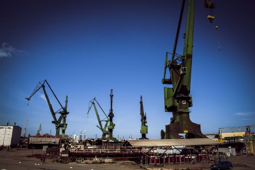 Large green single boom shipyard cranes in Gdansk shipyard, where Solidarity movement was founded in September 1980