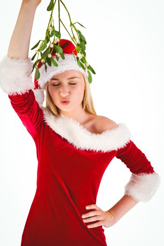 Festive cute blonde holding mistletoe