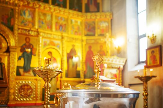 The font for the baptism of children in the Orthodox Church. Symbolic Orthodox gold cross on the cover font.