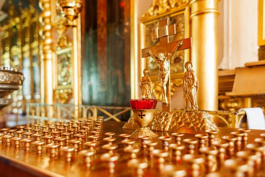 Golden candleholder in Orthodox church. Symbolic Orthodox gold cross with the crucifixion of Jesus.