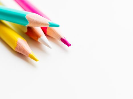 Colorful watercolor pencils on white background. School supplies with copy space. Kid's stationery. Back to school backdrop.